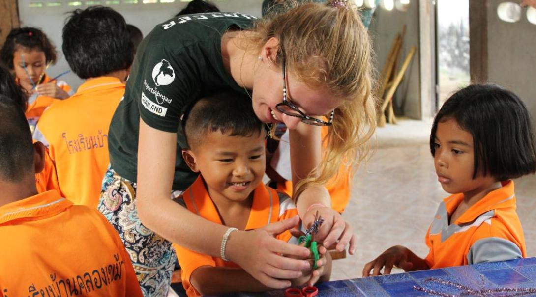 On an ethical volunteering opportunity, a Childcare volunteer in Thailand assists children during an arts and craft session.